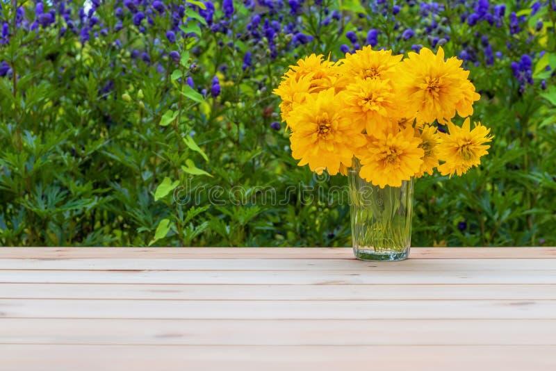 Lantlig livsstil Gula blommor i en fasetterad exponeringsglasdryckeskärl royaltyfria foton