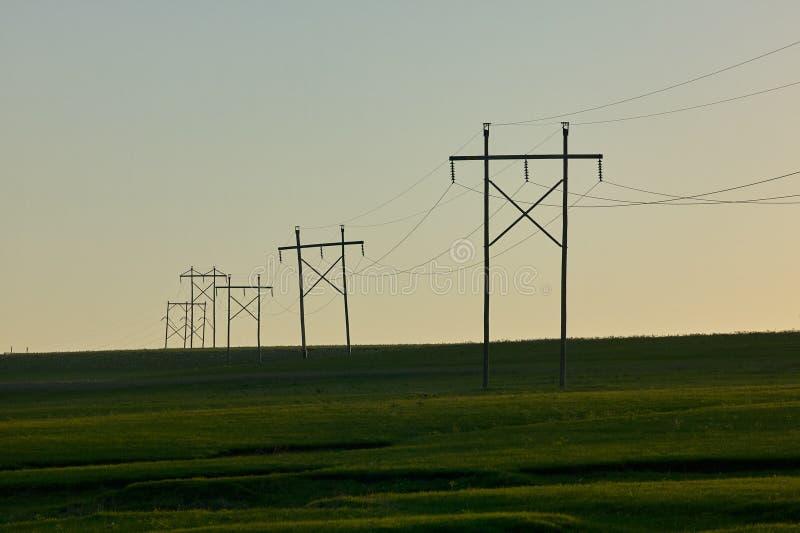 Lantlig plats med elektricitetspyloner på solnedgången arkivfoton