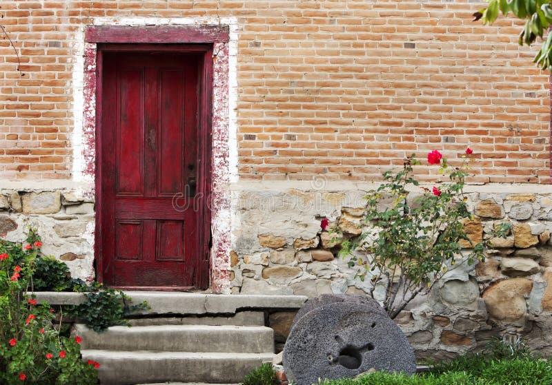 Lantlig röd byggnad för dörrtegelstensten royaltyfri foto