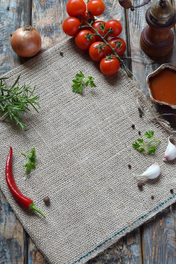 Lantlig sammansättning med peppar maler, tomatsouce, nya örter, grönsaker och kryddor Landsstil Baka eller laga mat bakgrund royaltyfri foto