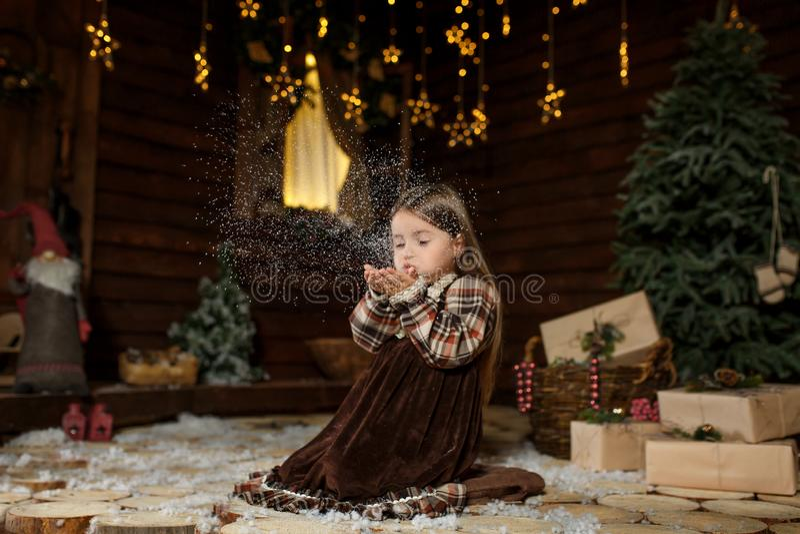 Lantlig stil klädde flickan som sitter på golvet, blåser snö från henne gömma i handflatan göra en önska Julsagamagi Den lyckliga arkivfoto