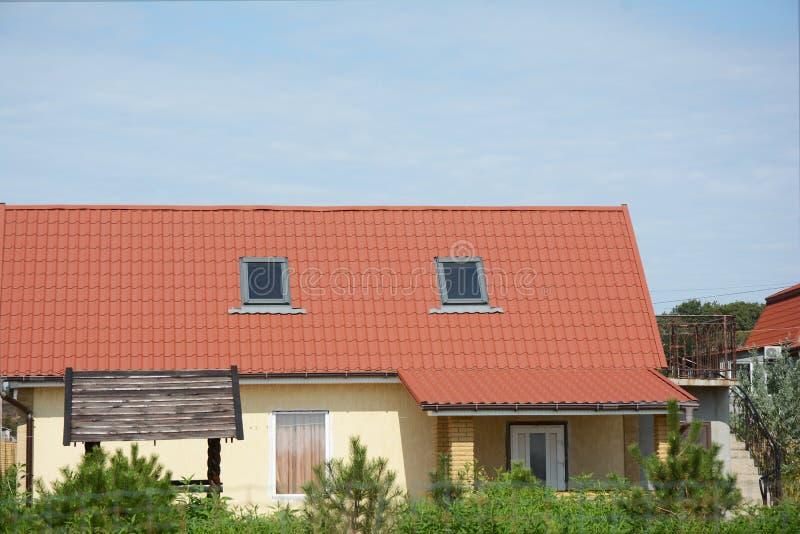 Lantlig stuga med röda metalltak- och lofttakfönsterfönster royaltyfri foto