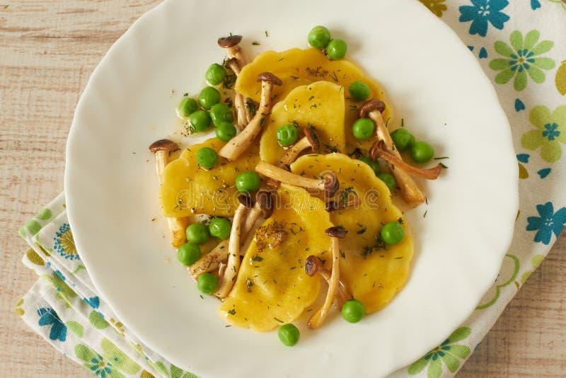 Lantlig tortellini med champinjoner och ärtor royaltyfria foton