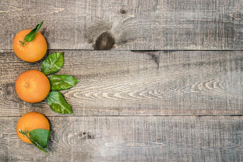 Lantlig träbakgrund med tre nya apelsiner med sidor fotografering för bildbyråer