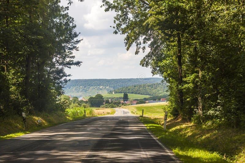 Lantlig väg för asfaltland i Tyskland till och med det gröna fältet arkivbild