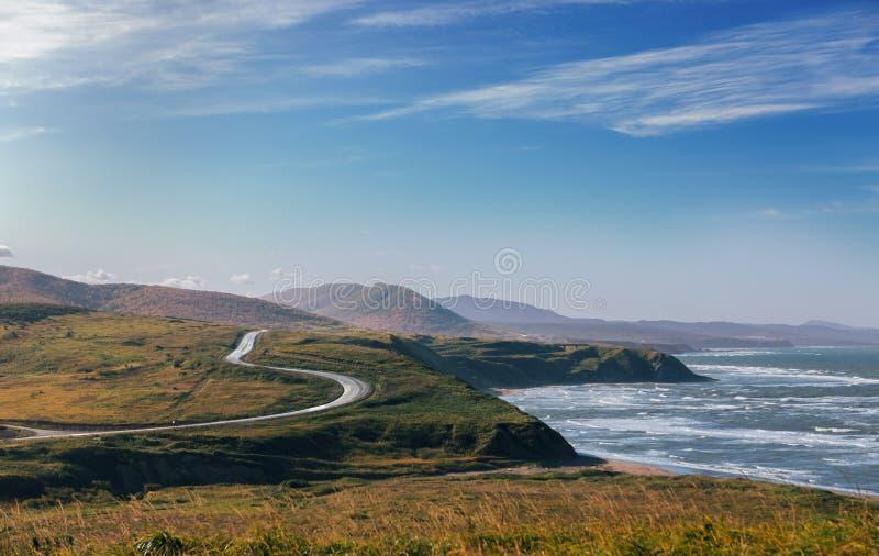 Lantlig väg som går nära kust av havet arkivfoto