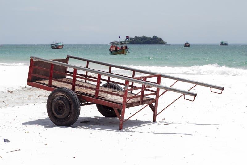 Lantlig vagn på den vita sandstranden Röd vagn vid ökensjösidan av den tropiska ön Lantlig asiatisk byrutin royaltyfria foton