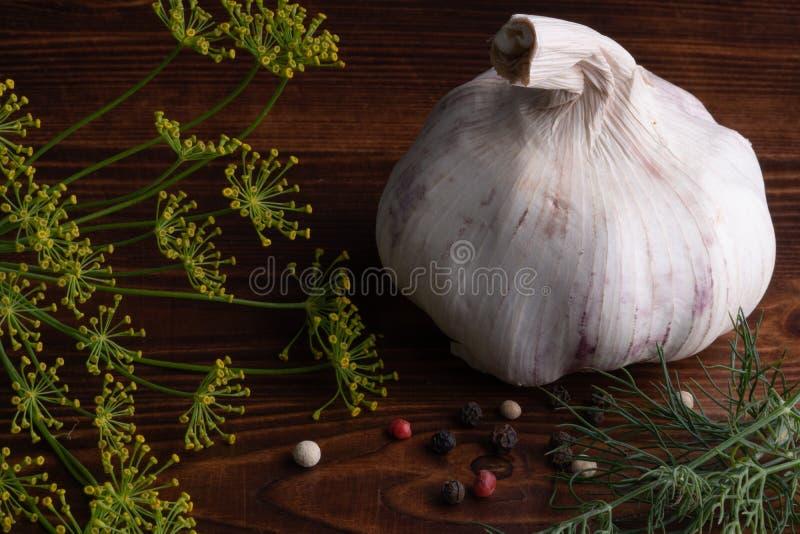 Lantlig vitlök med svart, vit röd peppar, dillpersilja på den gamla trätabellen royaltyfri bild