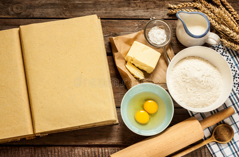 Lantliga ingredienser för kökbakningkaka och den tomma kocken bokar royaltyfria foton
