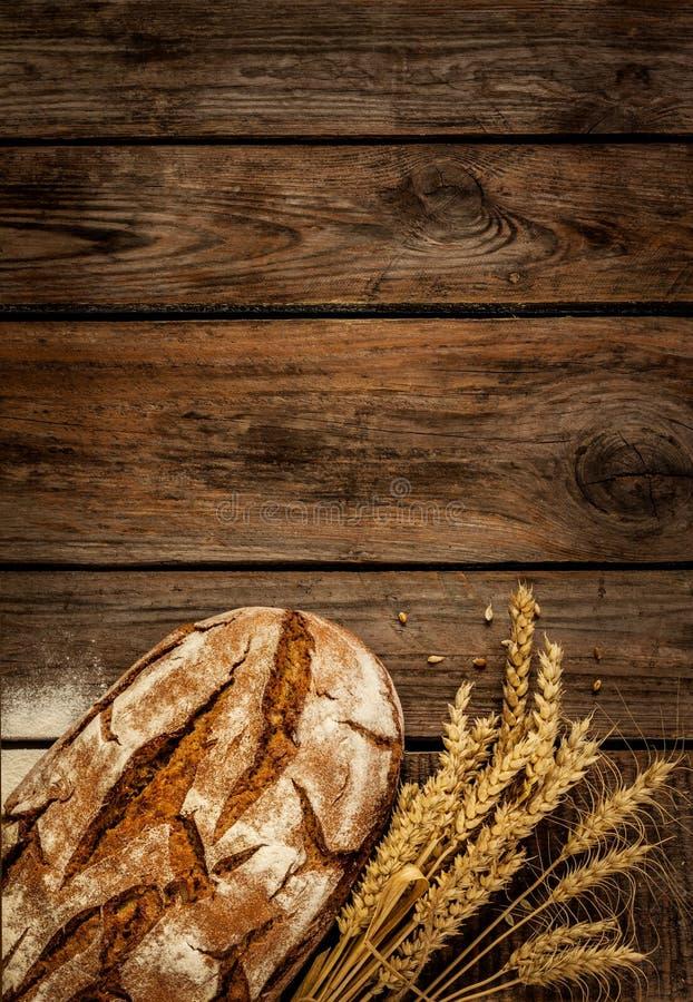 Lantligt bröd och vete på den wood tabellen för tappning royaltyfri bild