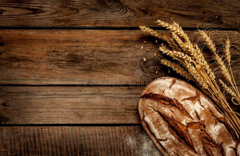 Lantligt bröd och vete på den wood tabellen för tappning arkivfoton