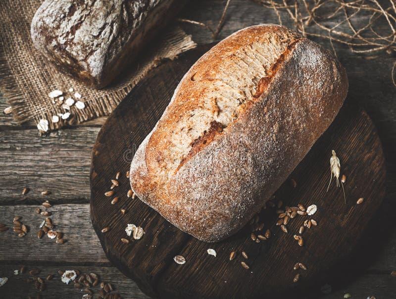Lantligt bröd och vete på en gammal tappning planked den wood tabellen dar royaltyfria foton
