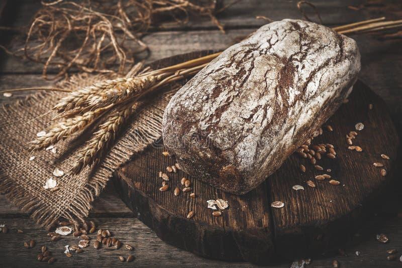 Lantligt bröd och vete på en gammal tappning planked den wood tabellen dar arkivfoton