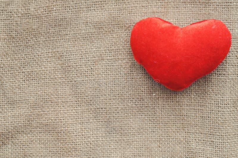 Lantligt förälskelsekort för tappning för valentin dag-röda flotta hjärta på säckväv closeup Top beskådar tonat sjaskig stil royaltyfri fotografi