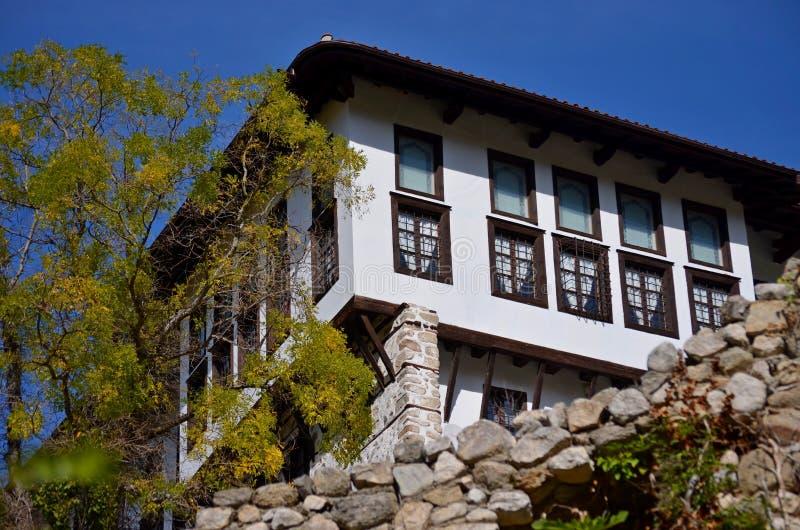 Lantligt hus, bak höstträd arkivfoton