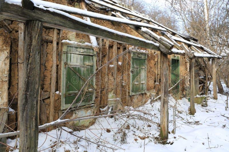 Lantligt hus för gammal lera i vintertid arkivfoto
