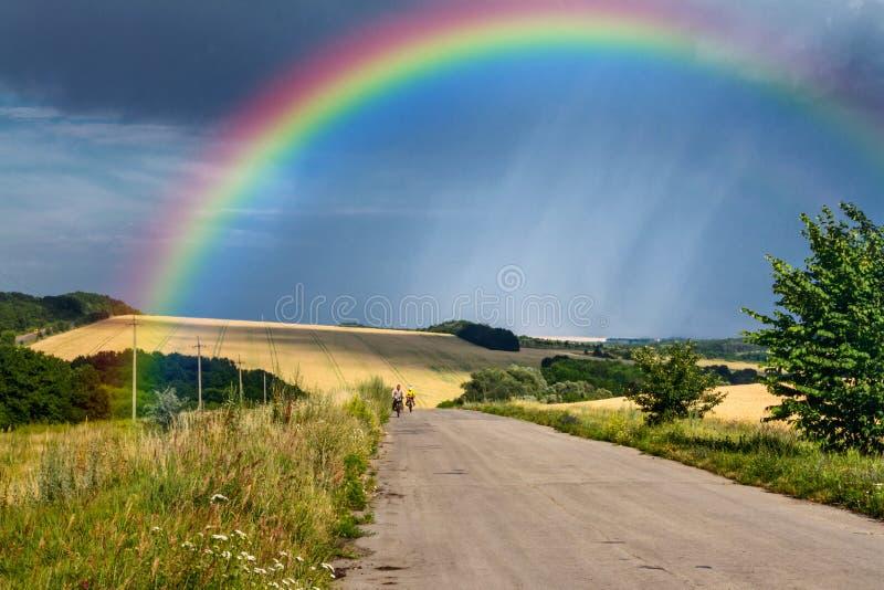 Lantligt landskap för sommar - väg med cyklister i strålarna av inställningssolen på den avlägsna regnbågen för bakgrund royaltyfria foton