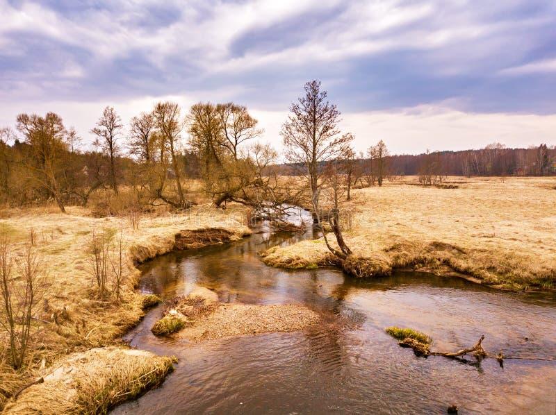 Lantligt landskap i April Liten flod i tidig vår royaltyfria foton