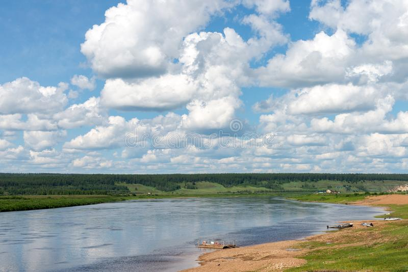 Lantligt landskap med byn och floden på den molniga dagen för sommar arkivfoto