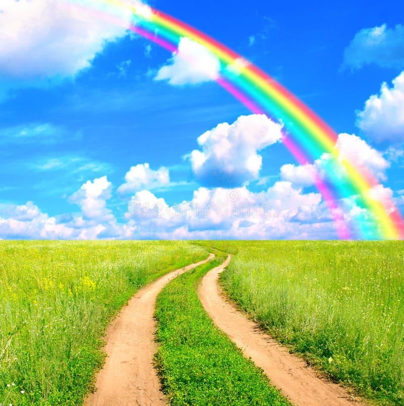 Lantligt landskap med den gamla vägen och regnbågen royaltyfria bilder