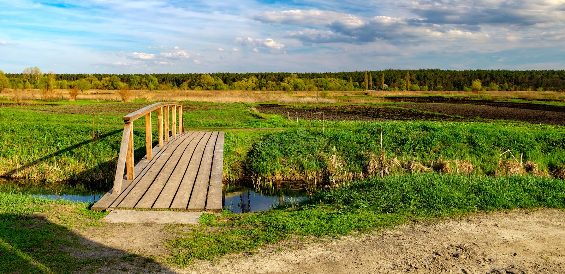 Lantligt landskap med den lilla floden och träbron arkivbilder