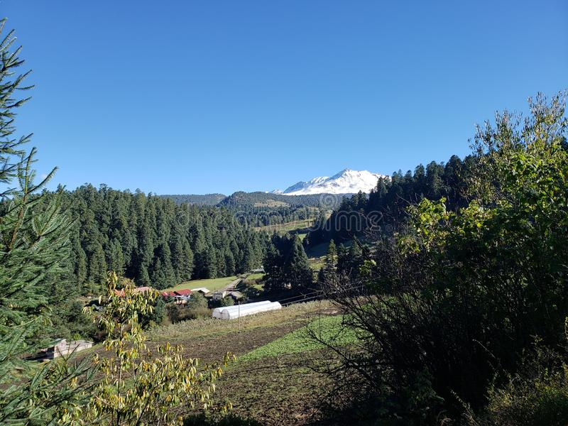 lantligt landskap med den Nevado de Toluca vulkan i vintersäsong och en solig dag royaltyfri bild