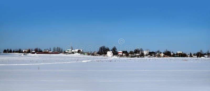 Lantligt landskap med en by på horisont efter snöfält under klar blå molnfri himmel på ljus panoramautsikt för solig dag arkivfoto