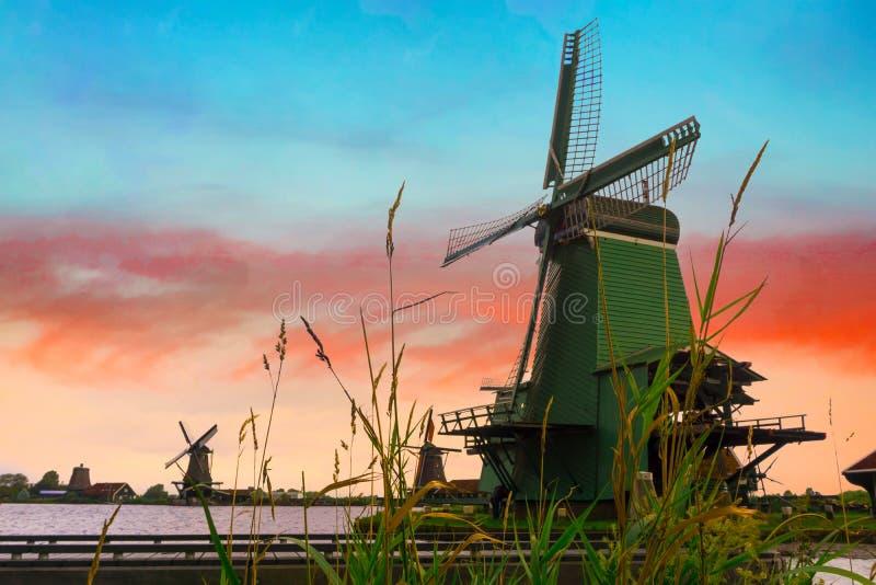 Lantligt landskap med väderkvarnen i Zaanse Schans Härlig solnedgångNetherland landscap arkivbild