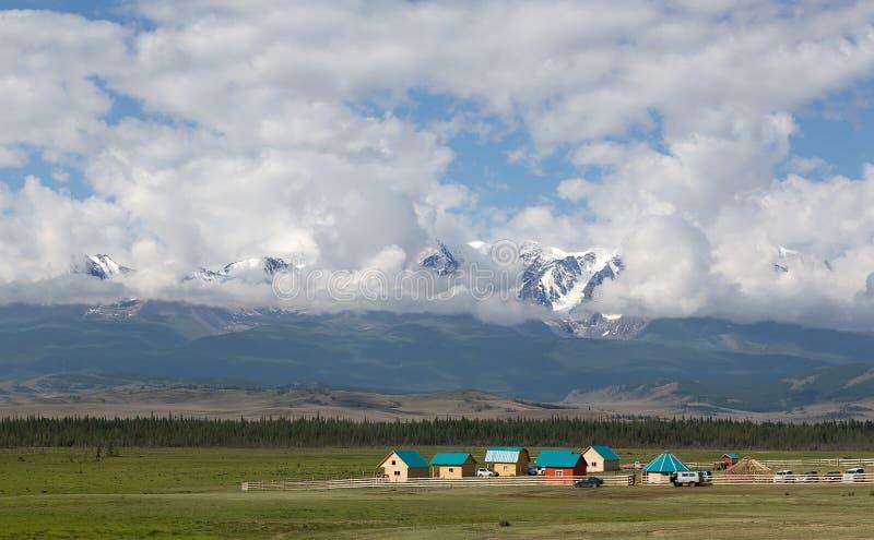 Lantligt landskap mot bakgrunden av höga snö-korkade berg royaltyfri bild