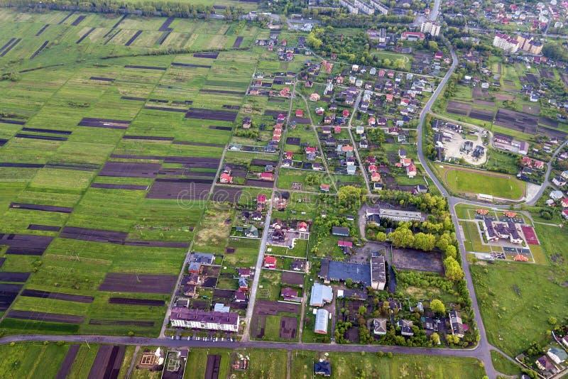 Lantligt landskap på vår- eller sommardag Flyg- sikt av den gröna och plogade fält, byn eller radhustak och vägar på soligt royaltyfri fotografi