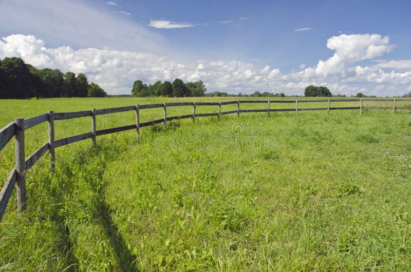 Lantligt landskapjordbruksmarkfält med trästaketet fotografering för bildbyråer