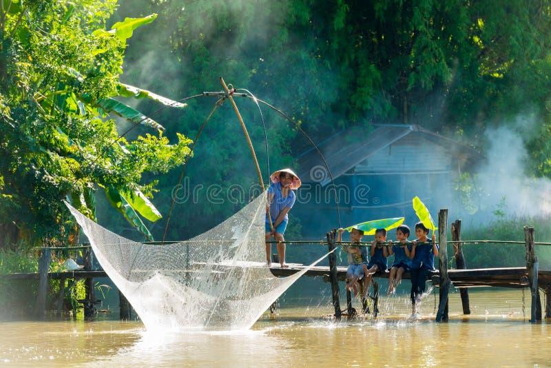Lantligt manfiske vid fisknät medan grupp av lantliga barn royaltyfri foto