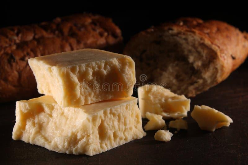Lantligt mogna Cheddarost och bröd arkivbild
