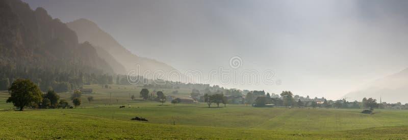 Lantligt schweiziskt bygdlandskap med lantgårdfält och dimmiga berg och skog i sen höst arkivfoton