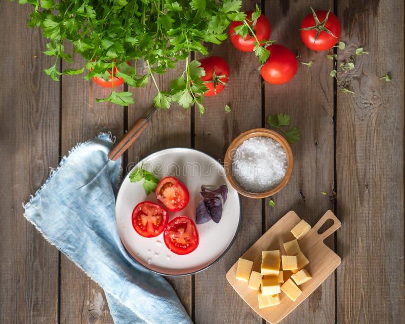 Lantligt skissa, lunch av huggen av ost på ett träbräde och röda tomater, en kvist av basilika Persiljagräsplaner, grov bomullstv arkivbilder