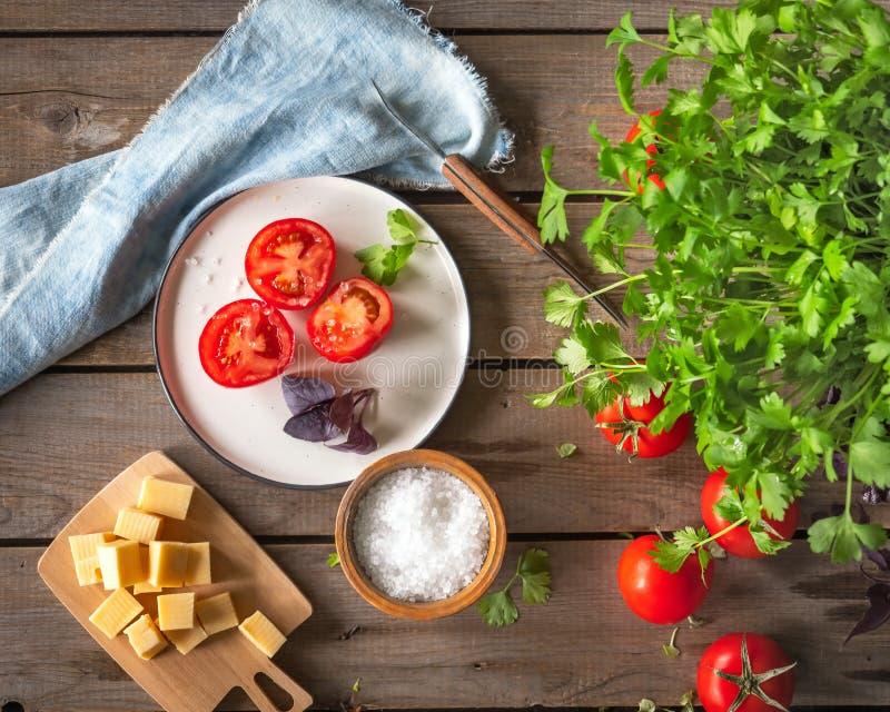 Lantligt skissa, lunch av huggen av ost på ett träbräde och röda tomater och en kvist av purpurfärgad basilika Persiljagräsplaner arkivbilder