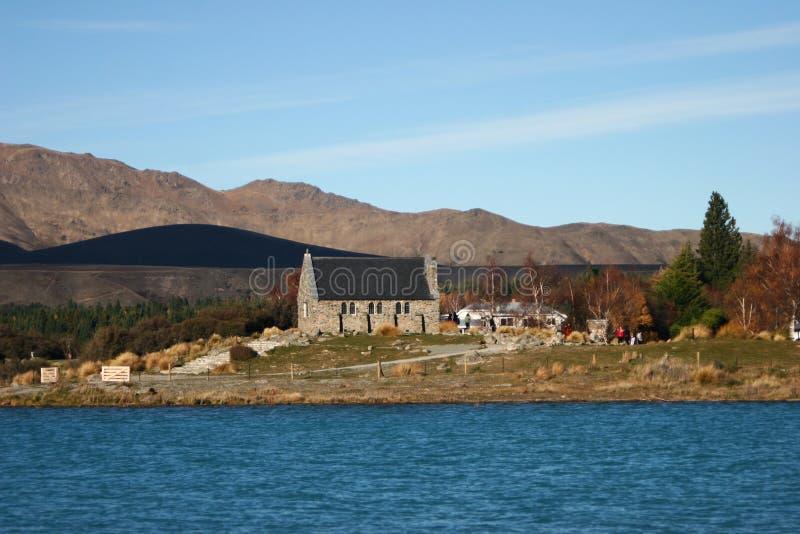 Lantligt stenhus med det sluttade taket på pittoresk landskapshoreline royaltyfri foto