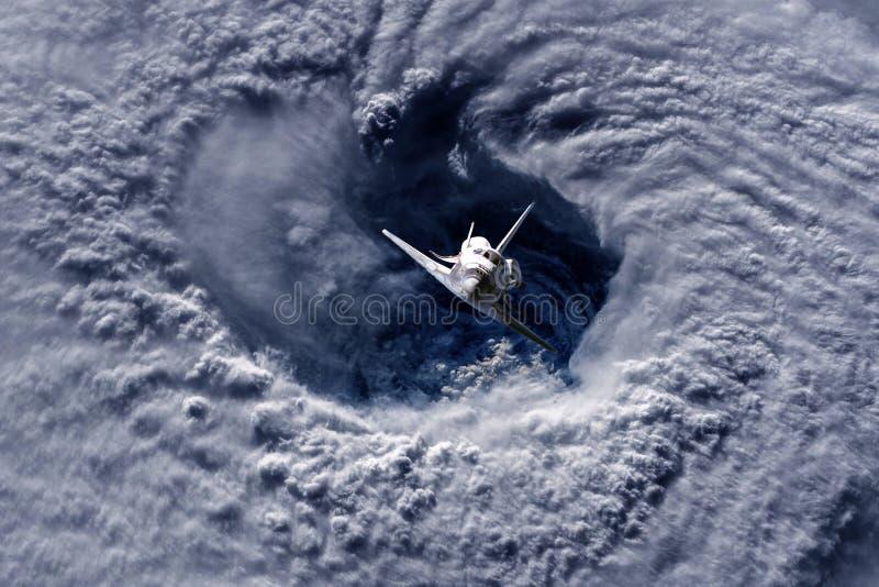 Lanzadera del vehículo espacial que vuela cerca de la tierra del huracán y de las nubes masivas en la atmósfera, imagen hecha de  fotos de archivo