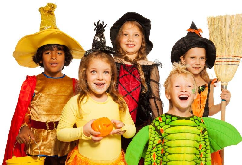 Lanzamiento cercano de cinco niños en disfraces de Halloween imagen de archivo