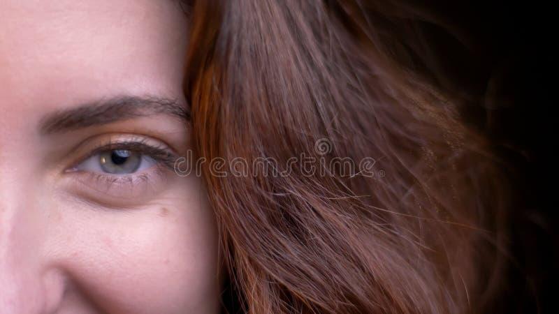 Lanzamiento de la mitad-cara del primer de la cara femenina caucásica atractiva joven que mira derecho la cámara con las luces de foto de archivo libre de regalías