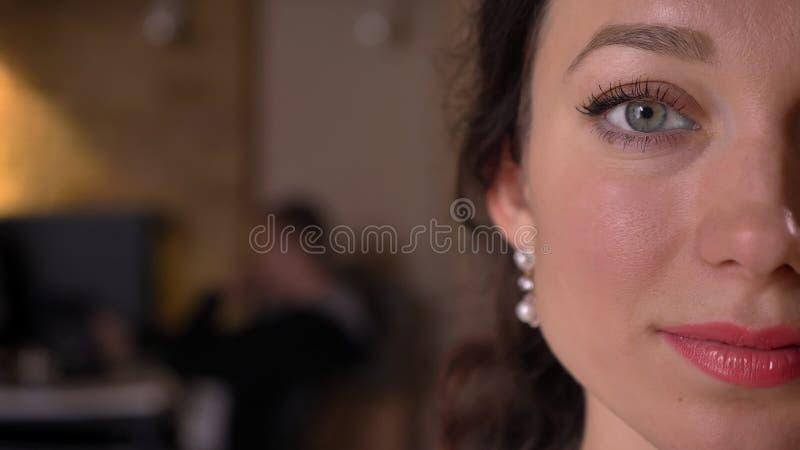 Lanzamiento de la mitad-cara del primer de la cara femenina caucásica bonita joven con los ojos que miran derecho la cámara con l imagen de archivo libre de regalías