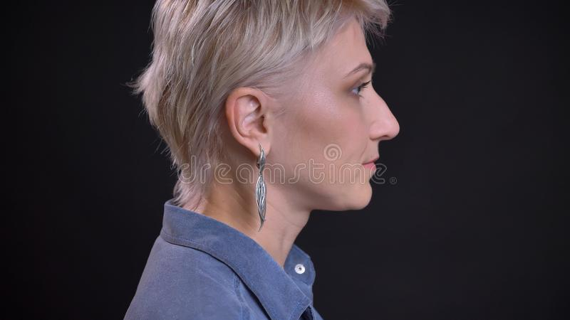 Lanzamiento de la vista lateral del primer de la cara femenina caucásica bonita adulta con el pelo rubio corto que mira adelante  foto de archivo
