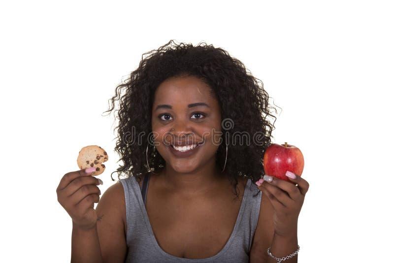 Lanzamiento del concepto sobre atención sanitaria de una mujer que elige entre una manzana y una galleta imagen de archivo