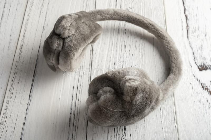 Lanzamiento del estudio de los manguitos mullidos grises del oído de la piel en la tabla de madera blanca fotografía de archivo
