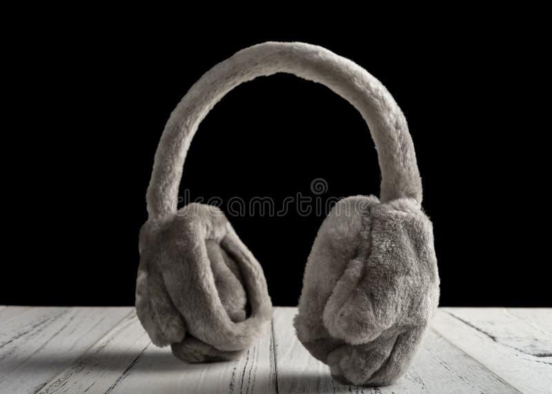 Lanzamiento del estudio de los manguitos mullidos grises del oído de la piel en la tabla de madera blanca foto de archivo libre de regalías