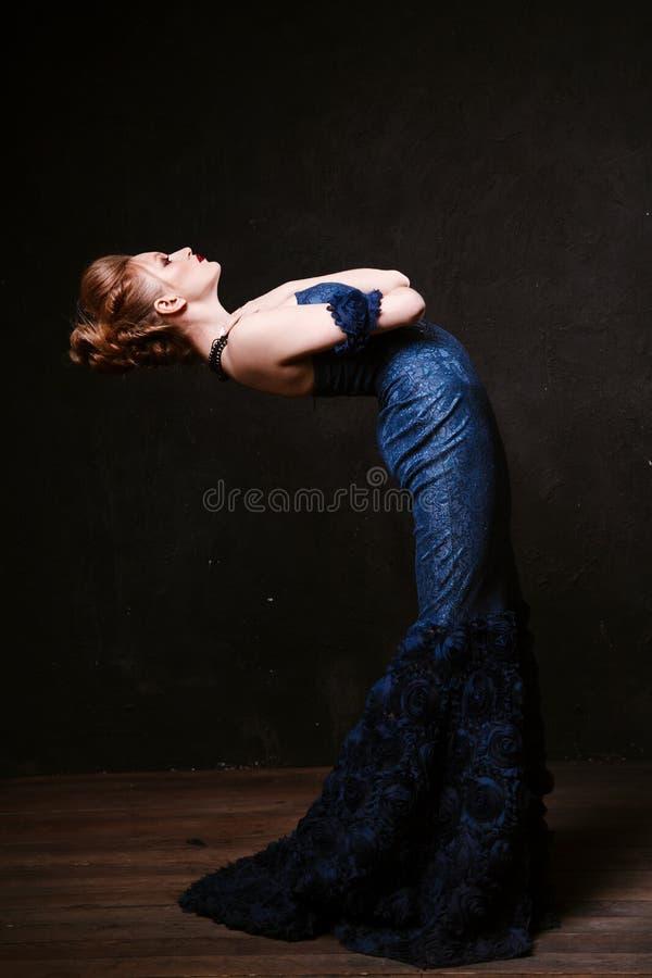Lanzamiento del estudio de presentar a la mujer en vestido azul largo Estilo retro fotos de archivo libres de regalías