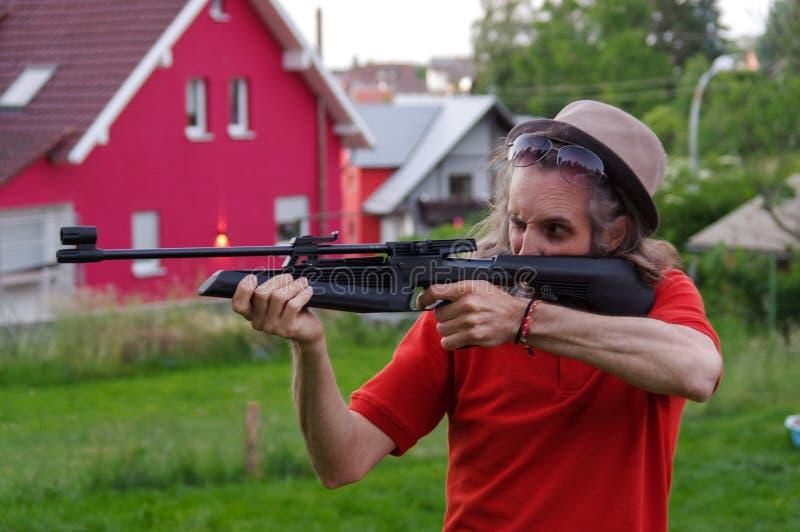 Lanzamiento del hombre joven con el rifle de aire afuera imágenes de archivo libres de regalías