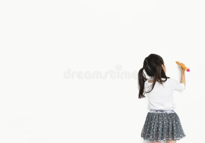 Lanzamiento del lápiz del dibujo de la niña fotos de archivo
