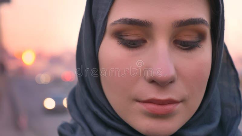Lanzamiento del primer de la cara femenina atractiva joven en el hijab que mira el plumón recto con la ciudad urbana en el fondo fotografía de archivo