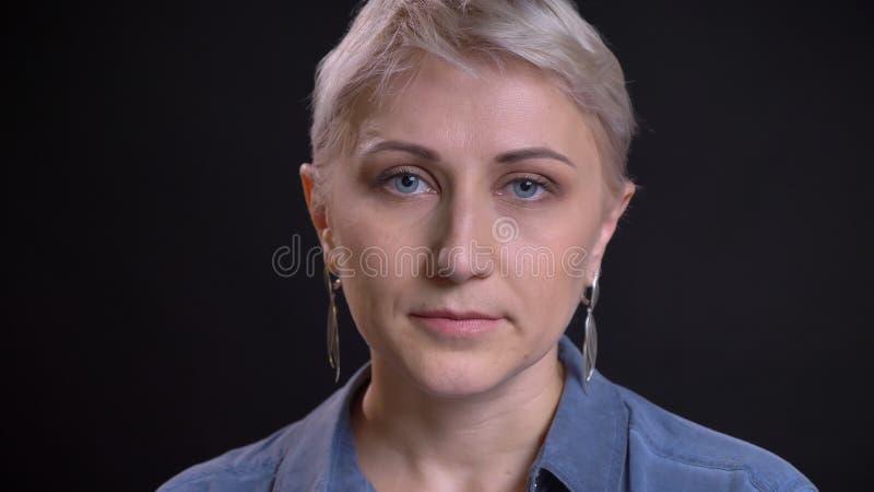 Lanzamiento del primer de la cara femenina caucásica atractiva adulta con el pelo rubio corto que mira la cámara con el fondo fotos de archivo libres de regalías